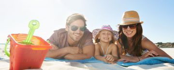 Shot of a young family lying on a towel at the beach